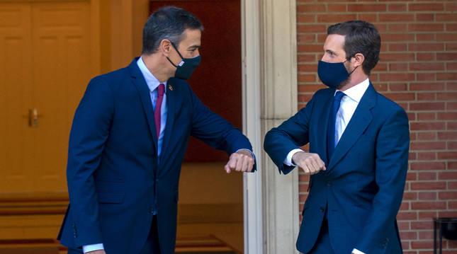 El presidente del Gobierno, Pedro Sánchez (i) y el presidente del PP, Pablo Casado, se saludan con el codo en el Palacio de Moncloa.