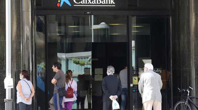 Foto de un grupo de personas haciendo cola en una oficina de Caixabank.