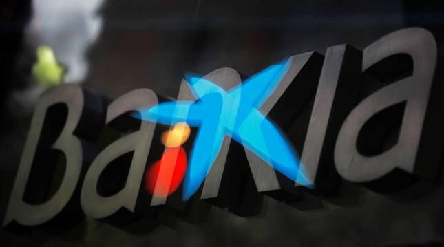 Fotografía de multiexposición que muestra los logotipos de las entidades bancarias Bankia y CaixaBank.