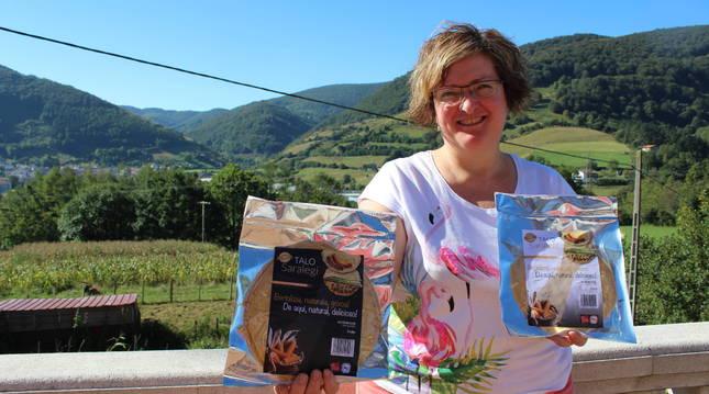 Cristina Saralegi, en la terraza del caserío Arro de Leitza, con sus talos envasados. Detrás, campo de maíz.
