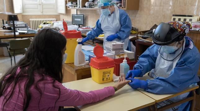 Las enfermeras del centro de salud Gayarre Ana Isabel Caparroso y Elizabeth Heredia realizan el test a una de las alumnas de 1º de Bachillerato C del colegio Jesuitas.