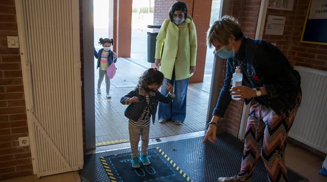 Daniela, de 4 años, desinfecta sus zapatos tras soltar a su madre, con abrigo amarillo, Marta Sampedro.