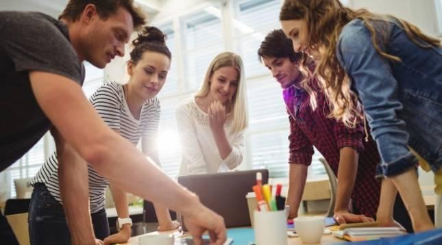 Varios jóvenes trabajan en un proyecto común en una oficina