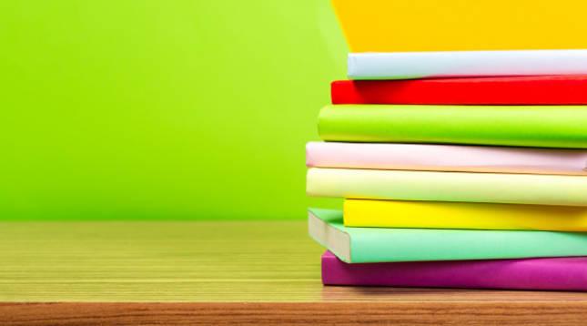 Varios libros de colores reposan apilados sobre una mesa