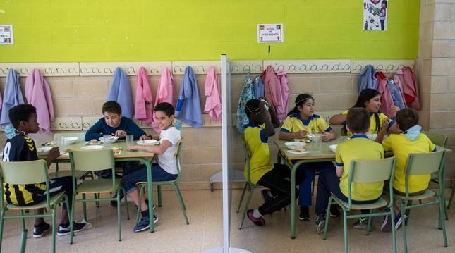 Foto de los alumnos comiendo con compañeros de su misma clase, grupo de convivencia estable, y se separan de los demás con mamparas para evitar el contagio del covid.