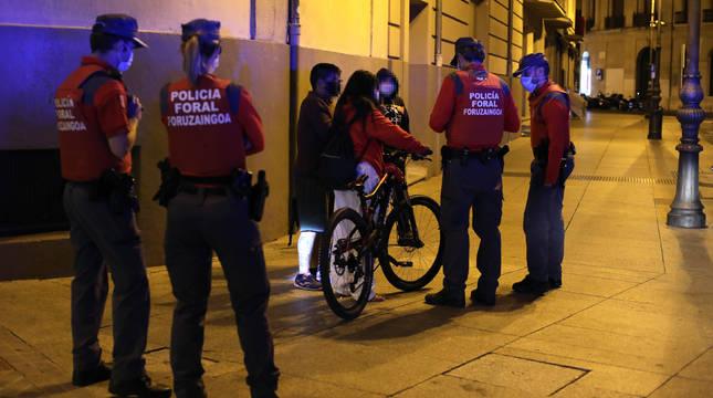 Agentes de Policía Foral comprueban el uso de mascarilla por unos jóvenes el sábado por la noche en Pamplona.