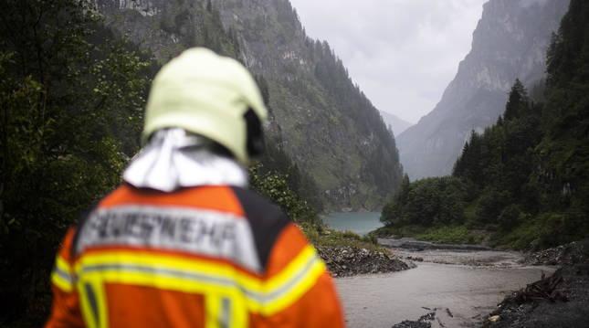 Foto de un miembro del servicio de emergencias observa la zona de la garganta de Parlitobel y el lago de Gigerwald, donde aparecieron los tres cuerpos el 12 de agosto.