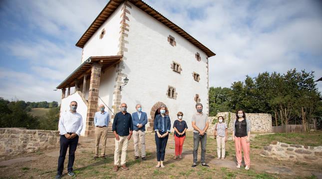 Foto de las autoridades y responsables de la restauración posando delante de la torre Dorrea en Irurita (Navarra).