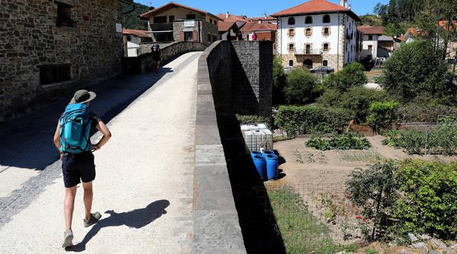 Un peregrino cruza el Puente de la Rabia de Zubiri situado en el recorrido del Camino de Santiago