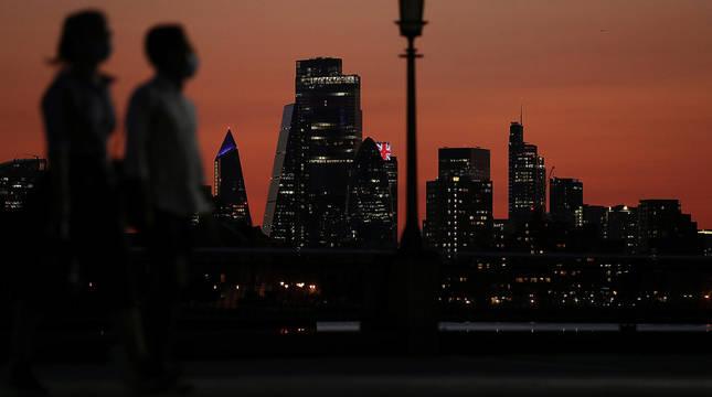 Dos personas caminan al atardecer, con el perfil de la City londinense al fondo.