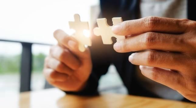 Una persona trata de encajar dos piezas de un puzle