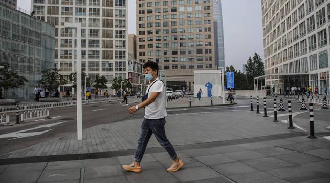 Foto de un hombre caminando por el distrito financiero de Pekín.