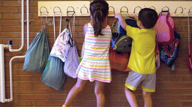 Foto de dos niños colgando sus mochilas en un colegio de Barcelona.