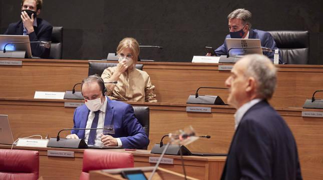 El parlamentario de EH Bildu Adolfo Araiz habla en el pleno del Parlamento de Navarra del 17 de septiembre de 2020 ante los parlamentarios de Navarra Suma Javier Esparza (primera fila), Isabel Olave, Alberto Bonilla (i) y Miguel Bujanda.