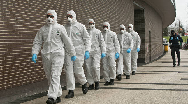 Foto de efectivos de la brigada móvil de la Ertzaintza, vestidos con buzos, entregando notificaciones a afectados por coronavirus en una calle de Vitoria en marzo 2020.