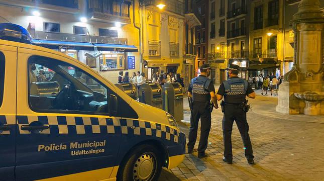 Dos agentes de la Policía Municipal de Pamplona patrullan en la plaza de Navarrería de Pamplona.