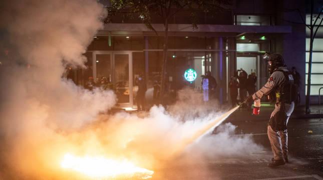 Un agente apaga las llamas de un cóctel molotov.