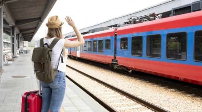 Una mujer saluda a los viajeros de un tren desde el andén