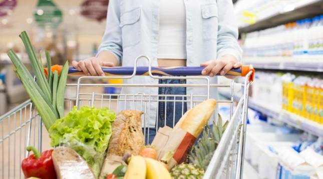 Una joven empuja un carro de la compra repleto de alimentos