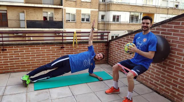 Los jugadores del Aspil Sergio González -a la izda.- y Ferran Plana realizan varios ejercicios físicos en la terraza de su casa en Tudela durante el confinamiento.