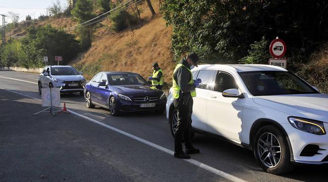 Agentes de Guardia Civil comprueban los justificantes de vehículos que salen de Funes.
