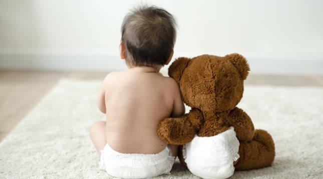 Imagen de un bebé con un osito de peluche