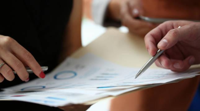 Imagen de dos personas manejando información financiera.