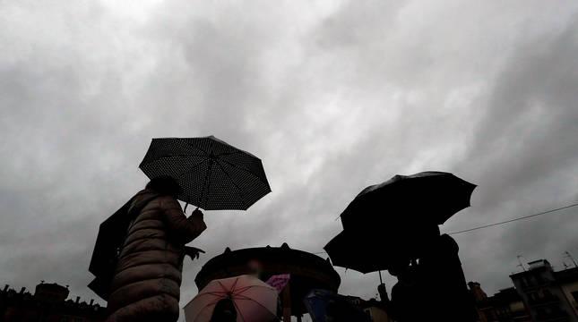 Un grupo de personas se protege con paraguas de la lluvia en Pamplona.