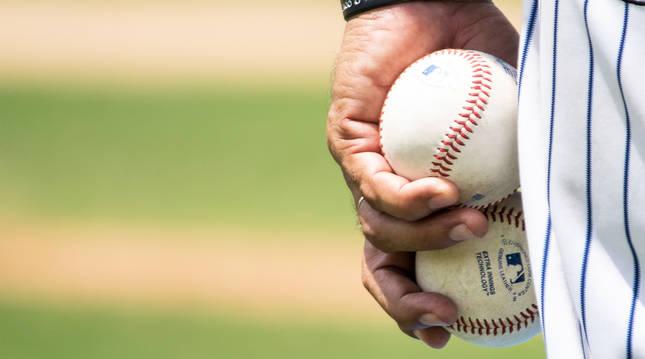 Un jugador de béisbol sujeta dos pelotas.