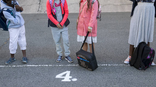 Foto de escolares con sus mochilas en un patio.