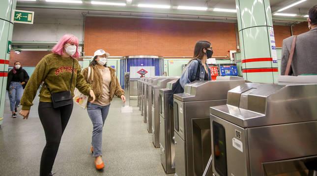 Foto de varias personas, en los tornos de salida del Metro de Ciudad Universitaria en Madrid.