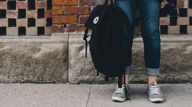 Foto de un menor, preparado para ir al colegio, con sus deportivas y su mochila.