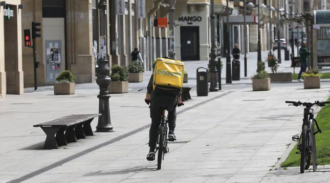 Un repartidor de Glovo atraviesa la avenida de Carlos III para una entrega.