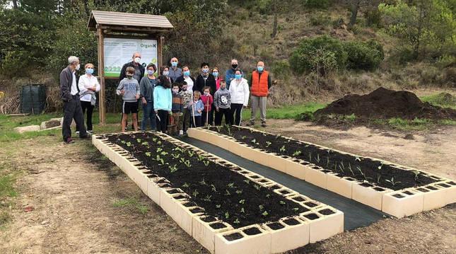 Foto de niños y mayores participantes en la plantación del huerto comunitario de Javier (Navarra).