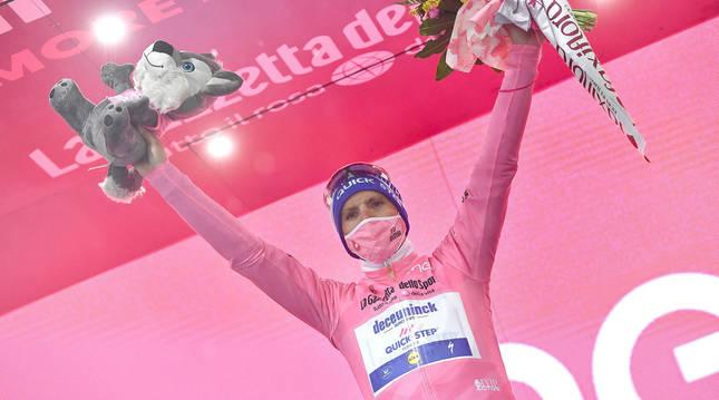 Foto del ciclista Joao Almeida, en el podio del Giro con la maglia rosa.