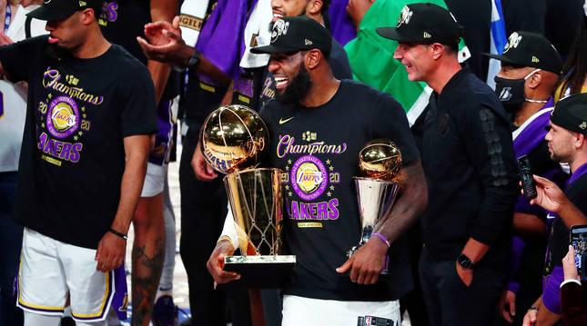 LeBron James posa con los trofeos de campeón de la NBA y de MVP.