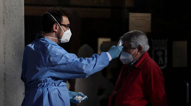 Foto de un sanitario tomando la temperatura a un hombre a su entrada al Centro Municipal de Mayores Príncipe de Asturias.