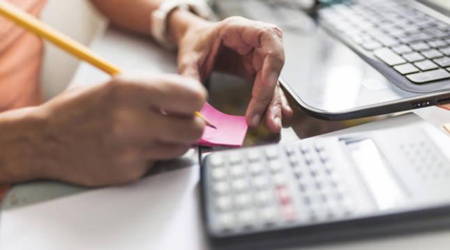 Imagen de una persona manejando documentación y una calculadora