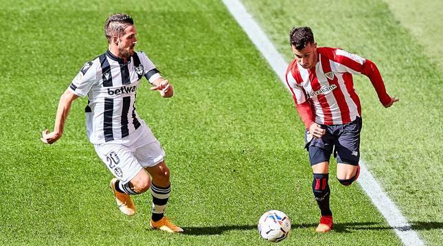 Berenguer persigue el balón ante la presión de un jugador del Levante.