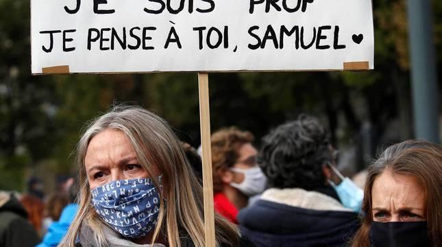 Una mujer sostiene en Lille una pancarta en recuerdo del profesor asesinado en París con el lema