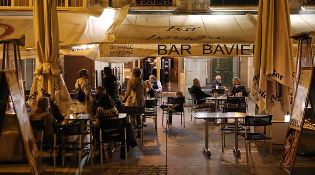 Varias personas, este lunes 19 de octubre por la tarde, en la terraza del Bar Baviera de la Plaza del Castillo.