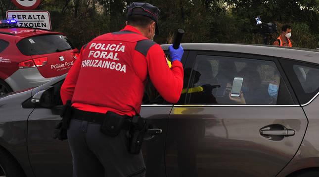 Una mujer enseña un justificante con su teléfono móvil al policía foral, durante el confinamiento perimetral que se estableció en Peralta.