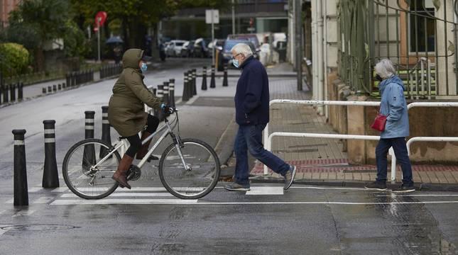 Transeúntes caminan con mascarillas por una calle de Pamplona.