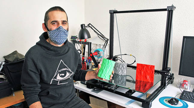 Martin Etxauri en el taller donde trabaja en su casa de Barañain. Junto a él, la impresora en 3D y una pieza de corteza de árbol en plástico.
