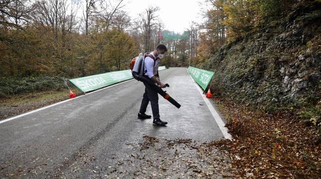 Una persona retira las hojas caídas en las últimas horas en la carretera de San Miguel de Aralar, por donde discurre la segunda etapa de la Vuelta.