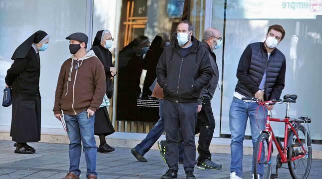 Transeúntes con mascarillas en la plaza de Merindades de Pamplona.