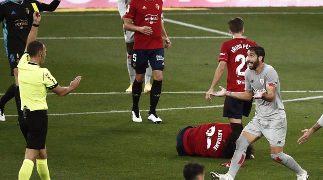 Raúl García protesta la amarilla al colegiado con Aridane Hernández tendido en el suelo.