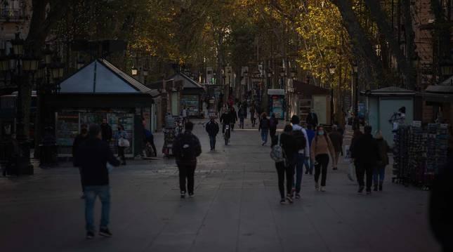 Foto de varias personas caminando por Las Ramblas de Barcelona en el primer amanecer después del toque de queda en la ciudad.