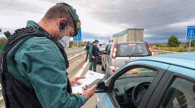 Agentes de la Guardia Civil controlan una carretera de acceso a Zaragoza para garantizar el cumplimiento del confinamiento.