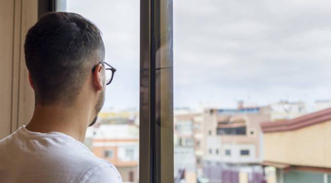 Un hombre mira a través de la ventana de su casa durante el confinamiento